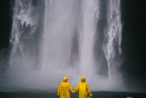 Paar hält Hände vor einem Wasserfall