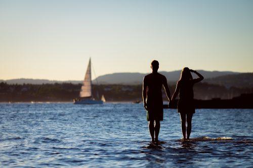 Paar hält Hände im ruhigen Wasser