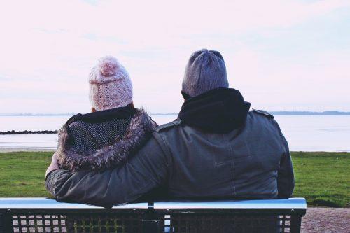 Junges Paar auf der Bank am Wasser